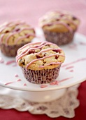 Three cranberry muffins with drizzle icing