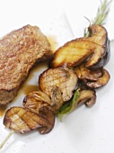 Grilled veal steak with mushrooms on rosemary skewer