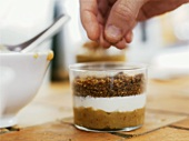 Hand sprinkling breadcrumbs on layered dessert in glass