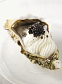 An oyster with whipped cream and caviar