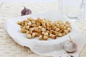 Croutons on kitchen paper with garlic bulbs