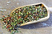 Herb and pepper mixture in a wooden scoop