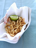 Fried calamari rings with lime on kitchen paper
