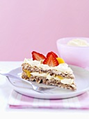 A piece of hazelnut meringue with strawberries and peaches