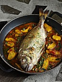 Whole bream with marinade cooked in a frying pan