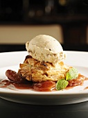 Filled pastry with walnut ice cream on plum compote