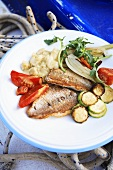 Fried red mullet fillets with vegetables in a boat