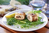 Grilled fish rolls on herbs with lemon