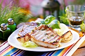 Grilled pork chops with onions on iceberg lettuce