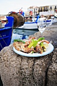 Grilled prawns with wine on a stone in a harbour