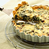 Spinach and cheese tart in the tin on a cake rack