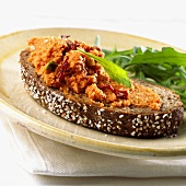 Pumpkin & nut spread on a slice of wholemeal bread with rocket