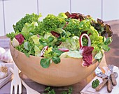 Mixed salad leaves with red onion in a wooden bowl