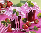 Two jars of strawberry jam with gift ribbons