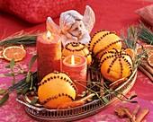 Mit Gewürznelken gespickte Orangen, Kerzen und ein Engel
