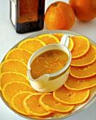Orangensauce in Sauciere auf einer Platte mit Orangenscheiben