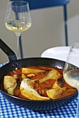 Haddock and fennel in wine sauce in a frying pan