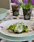 Soft cheese and asparagus roulade on salad leaves