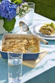 Potato and anchovy gratin in baking dish and on plate