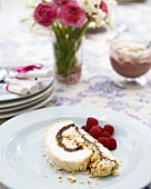 A piece of meringue roulade with cream & nut filling & raspberries