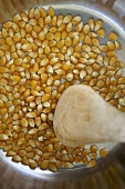 Making popcorn: stirring corn kernels in a pan