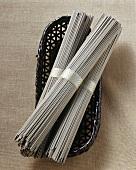 Soba noodles, in bundles on a wicker basket