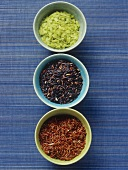 Red, green and black rice in small bowls