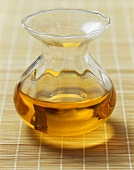 Groundnut oil in a glass carafe on a bamboo mat
