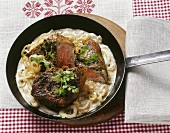 Steak in onion and white wine sauce in a frying pan