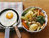 Braised vegetables in a dish, fried egg in frying pan