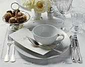 An elegant place-setting with menu and white roses