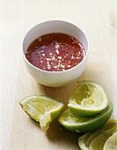 Chilisauce in einer Schüssel mit ausgepressten Limetten