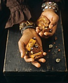 Woman holding financiers and jewellery in her hands