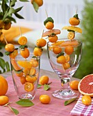 Kumquats, orange & grapefruit segments on skewers in glasses
