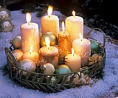 Candles and Christmas baubles on tray in snow (evening)