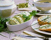 Herb butter in a small dish and on baguette