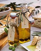 Zwei Glasflaschen mit Olivenöl, eingelegte Oliven, Ciabatta