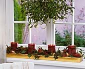 Adventsgesteck aus Efeu, Ilex, Picea, Misteln, Äpfeln, Kerzen