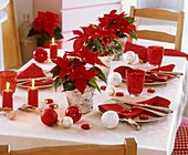 Christmas table decorated with poinsettias and baubles
