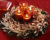 Adventskranz aus Zweigen, Efeu, Moosbeeren und Kerzen