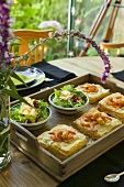 Puff pastry slices with prawns, green salads on tray