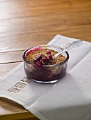 Cranberry crumble in a glass ramekin with a spoon