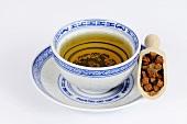 Dried dang shen root in wooden scoop with tea
