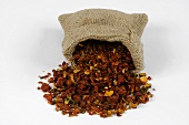 Dried gardenia fruits spilling out of a jute sack