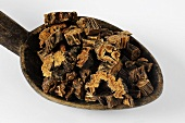 Pieces of dried gentian root on a wooden spoon