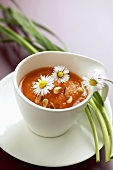 Carrot soup with pine nuts and daisies in a cup