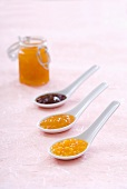 Strawberry and apricot jam, orange marmalade on spoons