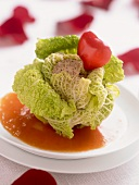 Savoy cabbage leaves stuffed with goose liver on tomato sauce