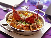 Lobster and scampi with bacon in a small pan