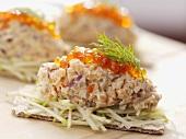 Fish tartare with salmon caviar on apple and crispbread